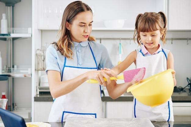 Mała dziewczynka w białym fartuchu pomaga matce przy robieniu ciasta i pieczenia w kuchni