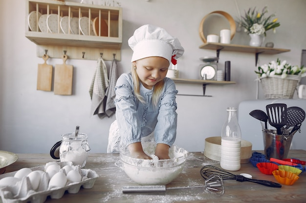 Mała dziewczynka w białym shef hat gotuje ciasto na ciastka