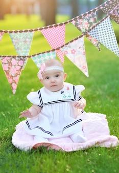 Mała dziewczynka w biel sukni obsiadaniu na trawie w parku