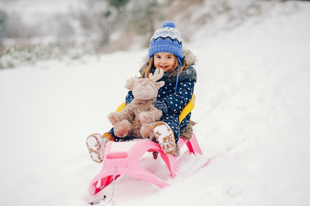 Mała dziewczynka w błękitnym kapeluszu bawić się w zima lesie