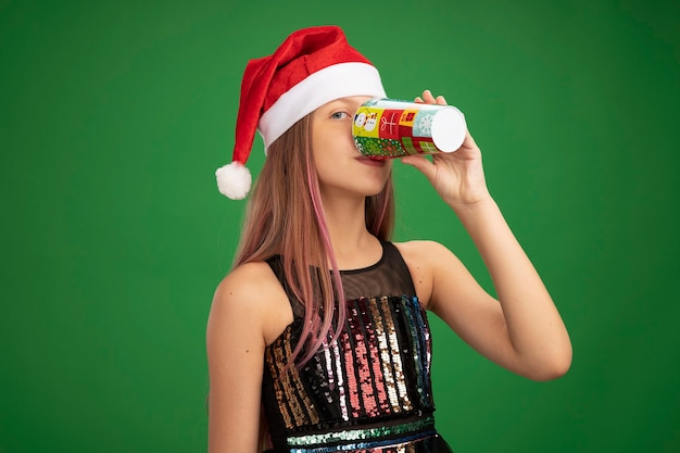 Mała dziewczynka w błyszczącej sukience i santa hat pije z kolorowego papierowego kubka stojącego nad zielonym tłem