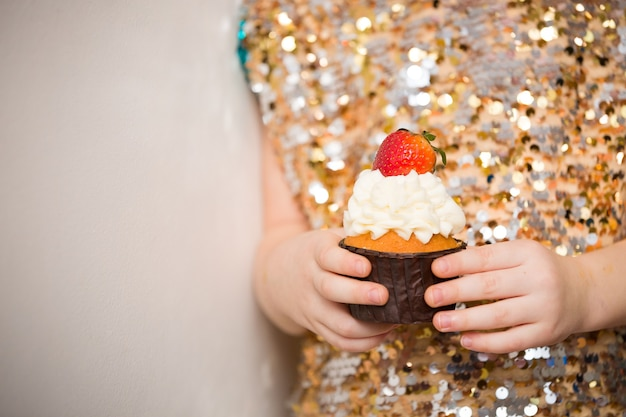 Mała dziewczynka w błyszczącej sukience trzyma piękną babeczkę na urodziny