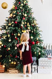 Mała dziewczynka w bordowej sukience z kokardą stoi w pobliżu choinki i czeka na boże narodzenie