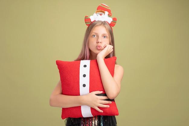 Mała dziewczynka w brokatowej sukience i opasce na głowę z mikołajem trzymającym zabawną poduszkę z ręką na brodzie, czekając stojąc nad zieloną ścianą