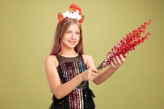 Mała dziewczynka w brokatowej sukience i opasce na głowę ze świętym mikołajem trzymającym gałęzie z czerwonymi jagodami, patrząc na bok, uśmiechając się radośnie, stojąc na zielonym tle