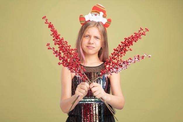 Mała dziewczynka w brokatowej sukience i opasce na głowę ze świętym mikołajem trzymającym gałęzie z czerwonymi jagodami patrząca na kamerę robiąca krzywe usta z rozczarowanym wyrazem stojącym nad zielonym tłem