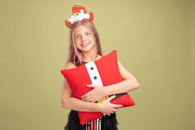 Mała dziewczynka w brokatowej sukience i opasce na głowę ze świętym mikołajem trzymającym śmieszną poduszkę patrzącą w kamerę uśmiechającą się radośnie stojącą nad zielonym tłem