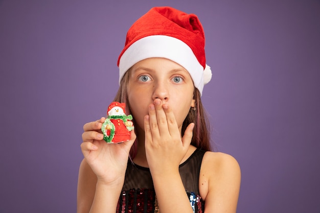 Mała dziewczynka w brokatowej sukience i santa hat pokazując świąteczną zabawkę patrząc na kamerę w szoku, zakrywając usta ręką stojącą na fioletowym tle