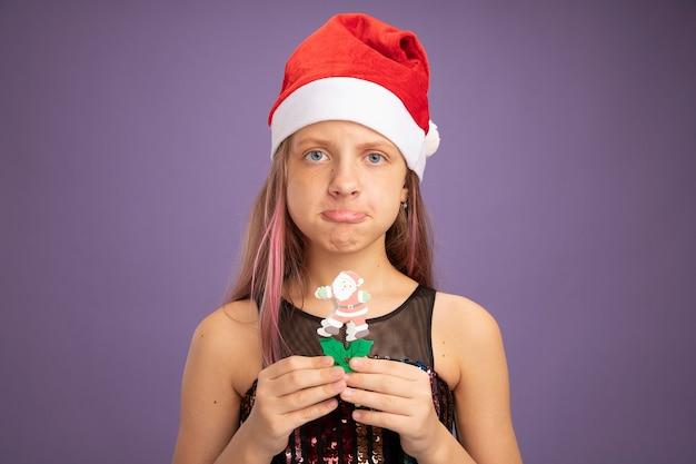 Mała dziewczynka w brokatowej sukience i santa hat pokazując świąteczną zabawkę patrząc na kamerę ze smutnym wyrazem ściskając usta stojąc na fioletowym tle