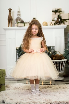 Mała dziewczynka w bujnej beżowej sukience