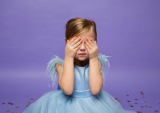 Mała dziewczynka w bujnej niebieskiej sukience zakryła oczy rękami na fioletowo