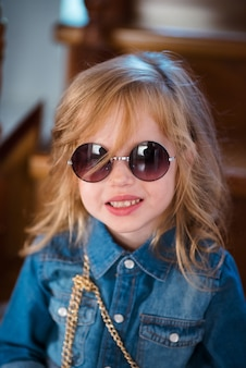 Mała dziewczynka w cajgach koszula i okulary przeciwsłoneczni pozuje i ono uśmiecha się.