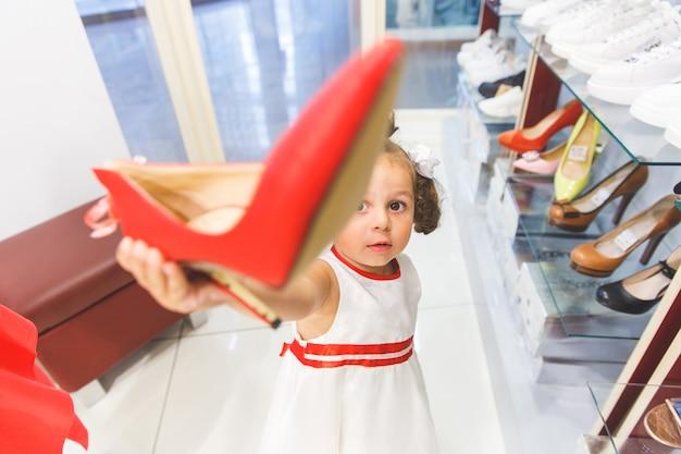 Mała dziewczynka w centrum handlowym wybiera buty