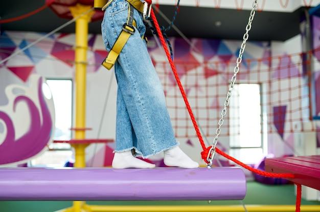 Mała dziewczynka w centrum rozrywki. dzieci bawiące się na terenie wspinaczkowym, dzieciaki spędzają weekend na placu zabaw, szczęśliwe dzieciństwo
