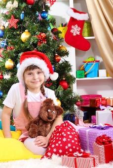 Mała dziewczynka w czapce mikołaja w pobliżu choinki w świątecznie urządzonym pokoju