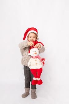 Mała dziewczynka w czapce mikołaja z bałwanem na białym tle, miejsce na tekst