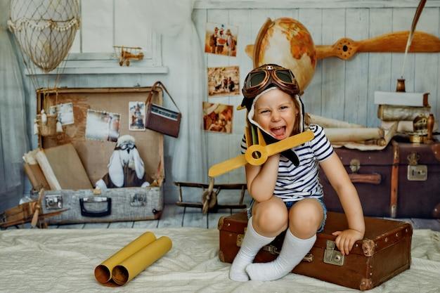 Mała dziewczynka w czapce siedzi na walizce w stylu retro i trzyma w ręku drewniany samolot
