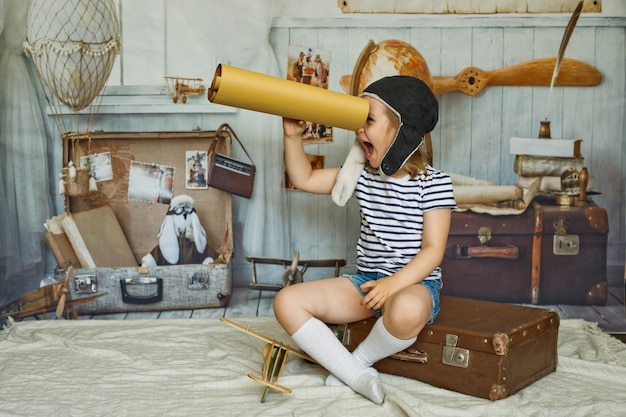 Mała dziewczynka w czapce siedzi na walizce w stylu retro i trzyma w ręku mapę jak teleskop