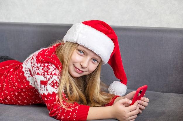 Mała dziewczynka w czapce świętego mikołaja rozmawia z telefonem.