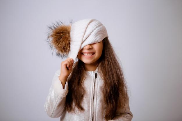 Mała dziewczynka w czapka zimowa uśmiecha się na białym tle