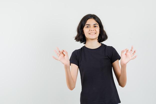 Mała dziewczynka w czarnej koszulce pokazuje znak ok i wygląda wesoło, widok z przodu.
