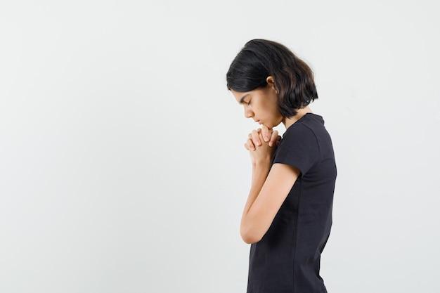 Mała dziewczynka w czarnej koszulce, ściskając ręce w geście modlitwy i patrząc z nadzieją.