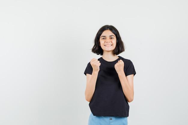 Mała dziewczynka w czarnej koszulce, spodenki pokazujące gest zwycięzcy i wyglądający wesoło, widok z przodu.