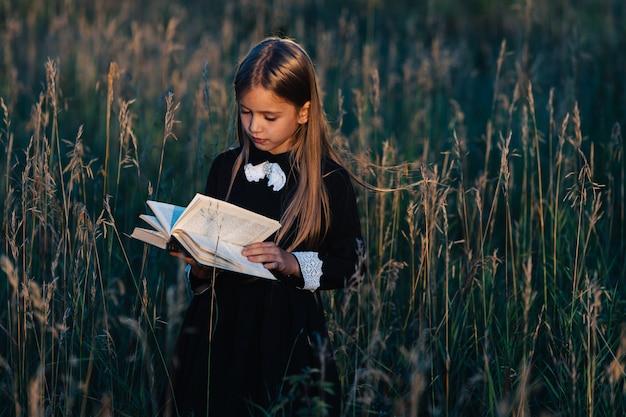 Mała dziewczynka w czarnej sukience stoi w wysokiej trawie i czyta zieloną książkę w świetle zachodzącego słońca.