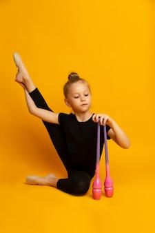 Mała dziewczynka w czarnym kostiumie kąpielowym rozciąga nogę, spogląda w dół i trzyma w ręku kluby sportowe