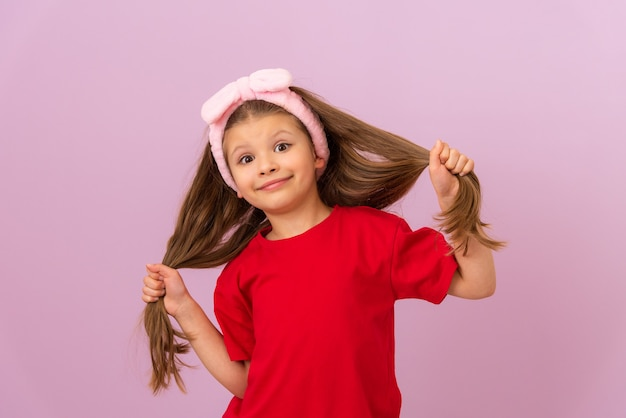 Mała Dziewczynka W Czerwonej Koszulce Ciągnie Włosy W Różne Strony. Premium Zdjęcia