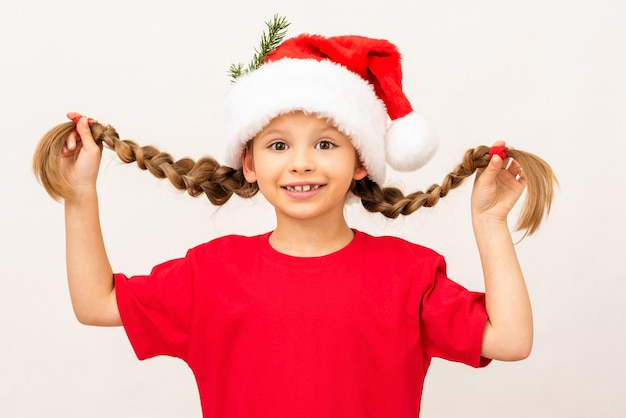 Mała dziewczynka w czerwonej koszulce i kapeluszu pozuje na białym tle.