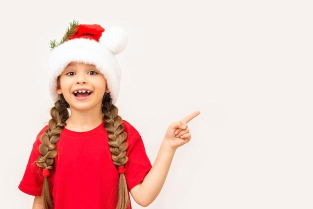 Mała dziewczynka w czerwonej koszulce i świątecznej czapce wskazuje na twoją reklamę.