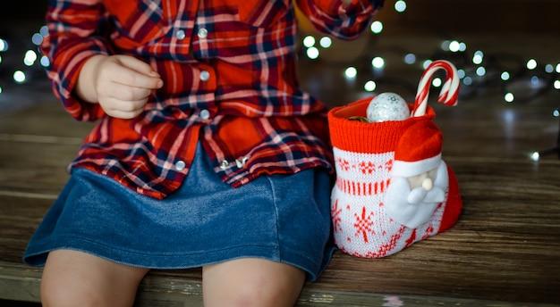 Mała dziewczynka w czerwonej kraciastej koszuli i dżinsowej spódnicy otwiera słodycze z jej świątecznego prezentu, siedząc na drewnianym stole. koncepcja bożego narodzenia rano. ścieśniać.