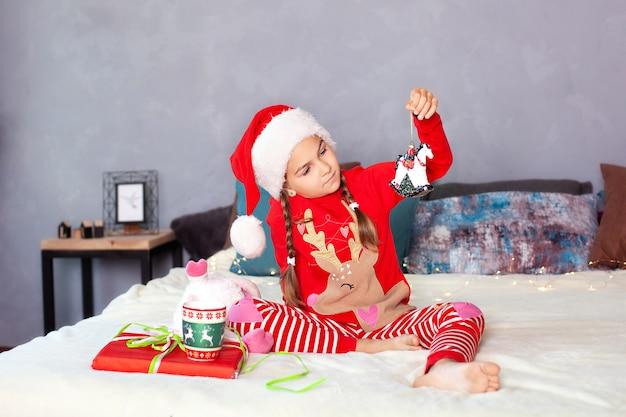 Mała dziewczynka w czerwonej piżamie i kapeluszu santa