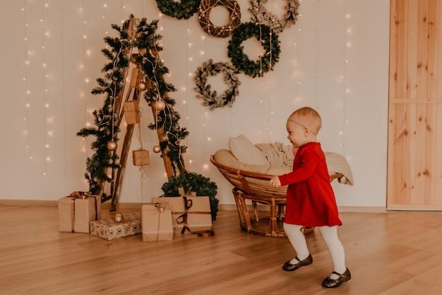 Mała dziewczynka w czerwonej sukience prowadzi lekki minimalizm w stylu mieszkania. dziecko stoi przy białej ścianie z girlandami choinka z zapakowanymi prezentami. boże narodzenie. nowy rok wnętrze. walentynki obchody