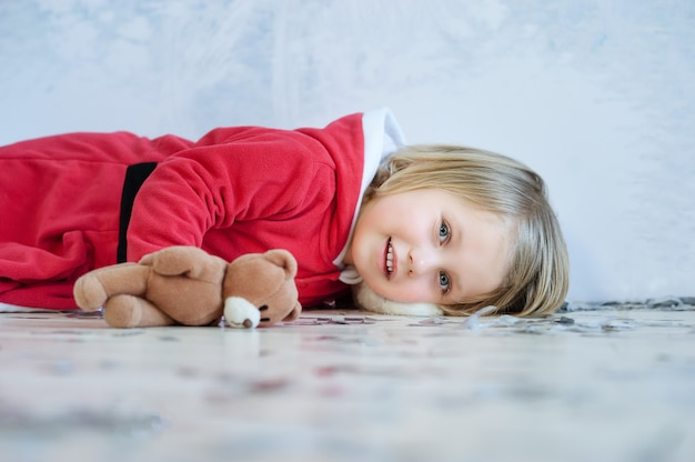 Mała dziewczynka w czerwonej sukience w domu wnętrze czeka na mikołaja