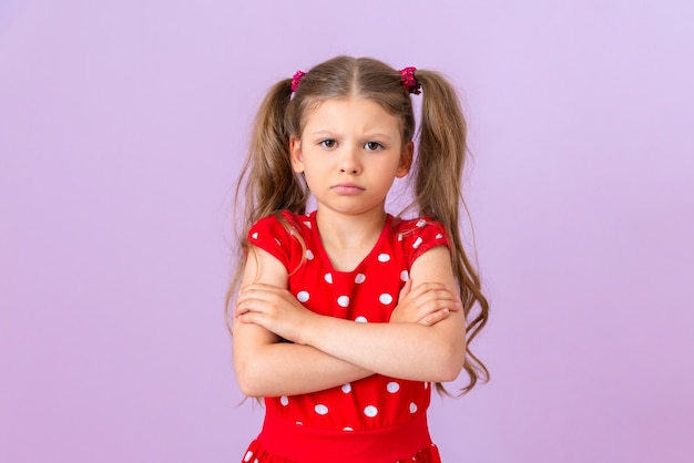 Mała dziewczynka w czerwonej sukience w kropki jest bardzo urażona