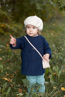 Mała dziewczynka w czerwonym płaszczu na jesień trzyma liście
