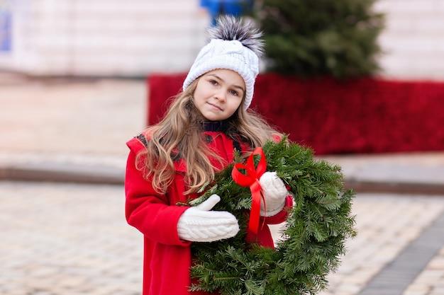 Mała dziewczynka w czerwonym płaszczu z wieniec bożonarodzeniowy