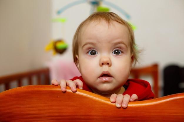 Mała dziewczynka w czerwonym swetrze, pięknie się uśmiecha, w łóżeczku, bawi się i ma zabawne, emocjonalne zdjęcie