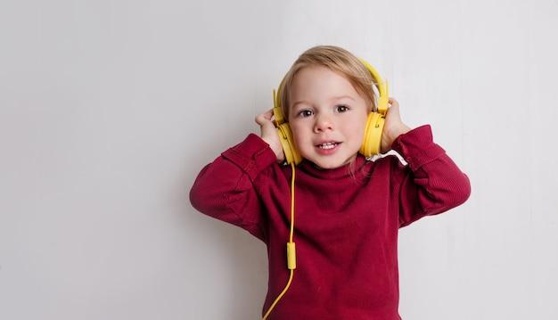 Mała dziewczynka w czerwonym swetrze słucha muzyki w słuchawkach i śmieje się na białym tle.