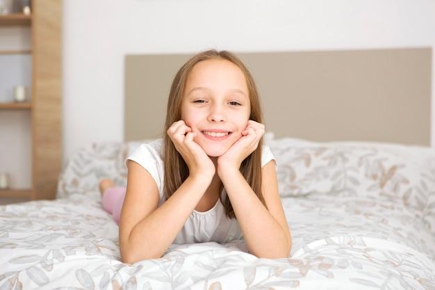 Mała dziewczynka w dobrym nastroju w piżamie w sypialni