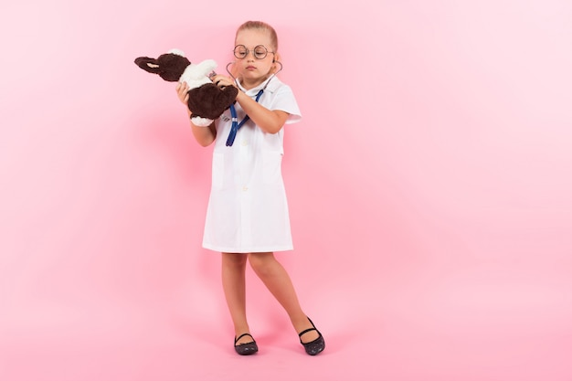 Mała dziewczynka w doktorskim kostiumu z zabawką