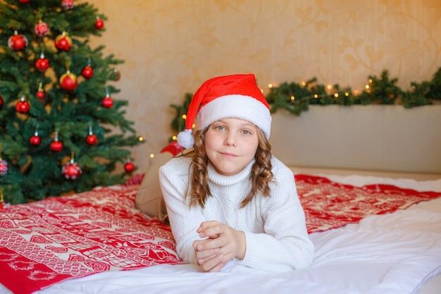 Mała dziewczynka w domu, leżąc na łóżku w sypialni w kapeluszu santa