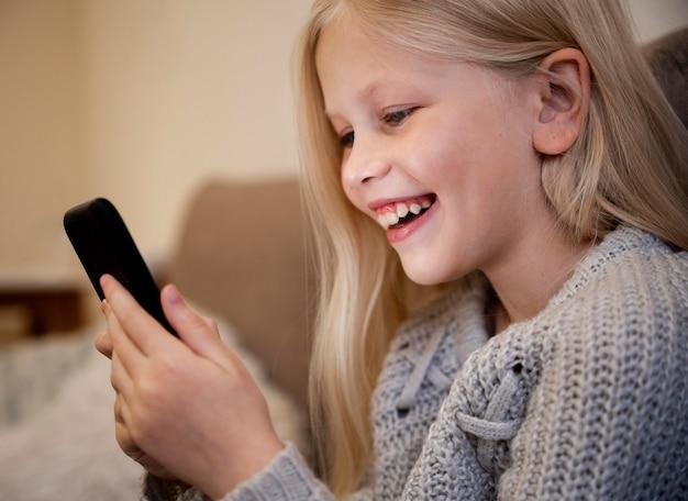 Mała dziewczynka w domu przy użyciu smartfona