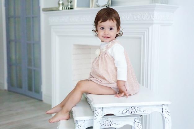 Mała dziewczynka w domu siedzi na nowoczesnym przytulnym szarym krześle, relaksując się w białym salonie