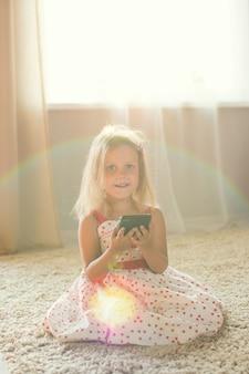 Mała dziewczynka w domu ze smartfonem