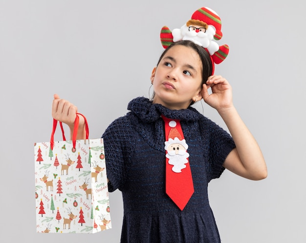 Mała dziewczynka w dzianinowej sukience ubrana w czerwony krawat z zabawną świąteczną obwódką na głowie trzyma papierową torbę z prezentem świątecznym, patrząc zdziwiona