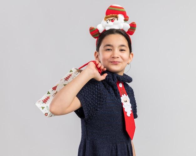 Mała dziewczynka w dzianinowej sukience ubrana w czerwony krawat z zabawną świąteczną obwódką na głowie trzyma papierową torbę z prezentem świątecznym, wyglądająca szczęśliwie i pozytywnie