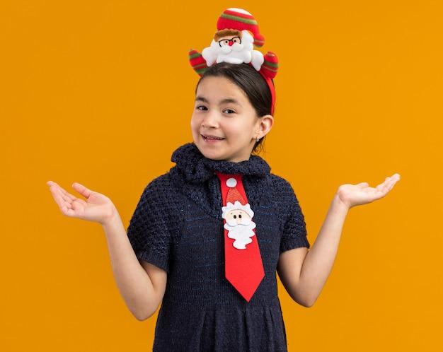 Mała dziewczynka w dzianinowej sukience ubrana w czerwony krawat z zabawną świąteczną obwódką na głowie, wyglądająca na szczęśliwą i radosną uśmiechniętą, rozkładającą ramiona na boki